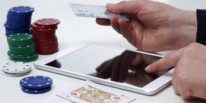 a person gambling with an ipad and a credit card