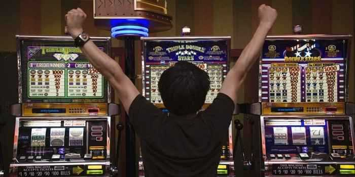 man cheering in front of slot machines
