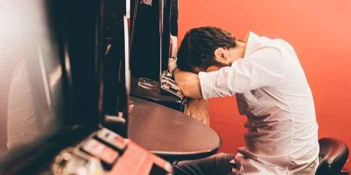 sad gambler in a casino at a slot machine